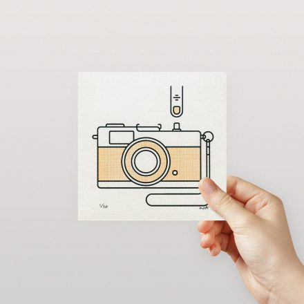 Hand holding a 5x5 inch minimal print of an Olympus Trip by Things by us