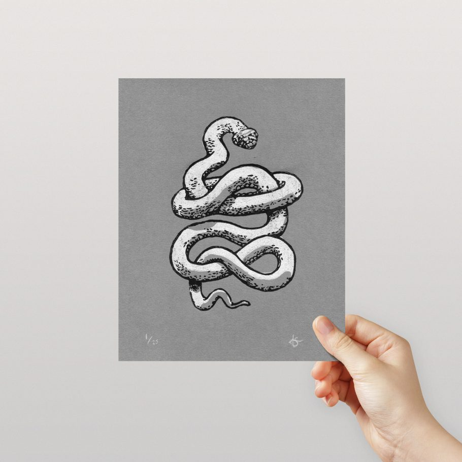 Hand holding a snake linocut print on grey paper - Things by us